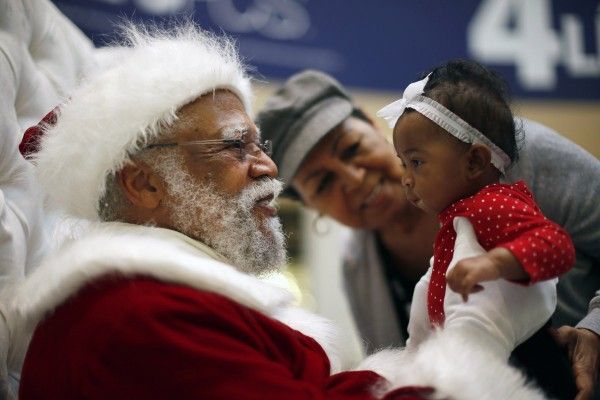 African American Santa Claus Langston Patterson, 77, greets four-month-old Raelyn Price at Baldwin Hills Crenshaw Plaza mall in Los Angeles